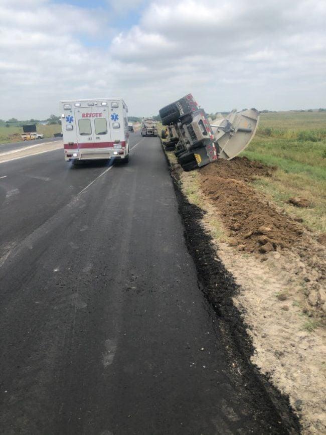 Truck tips onto side, near Cortland