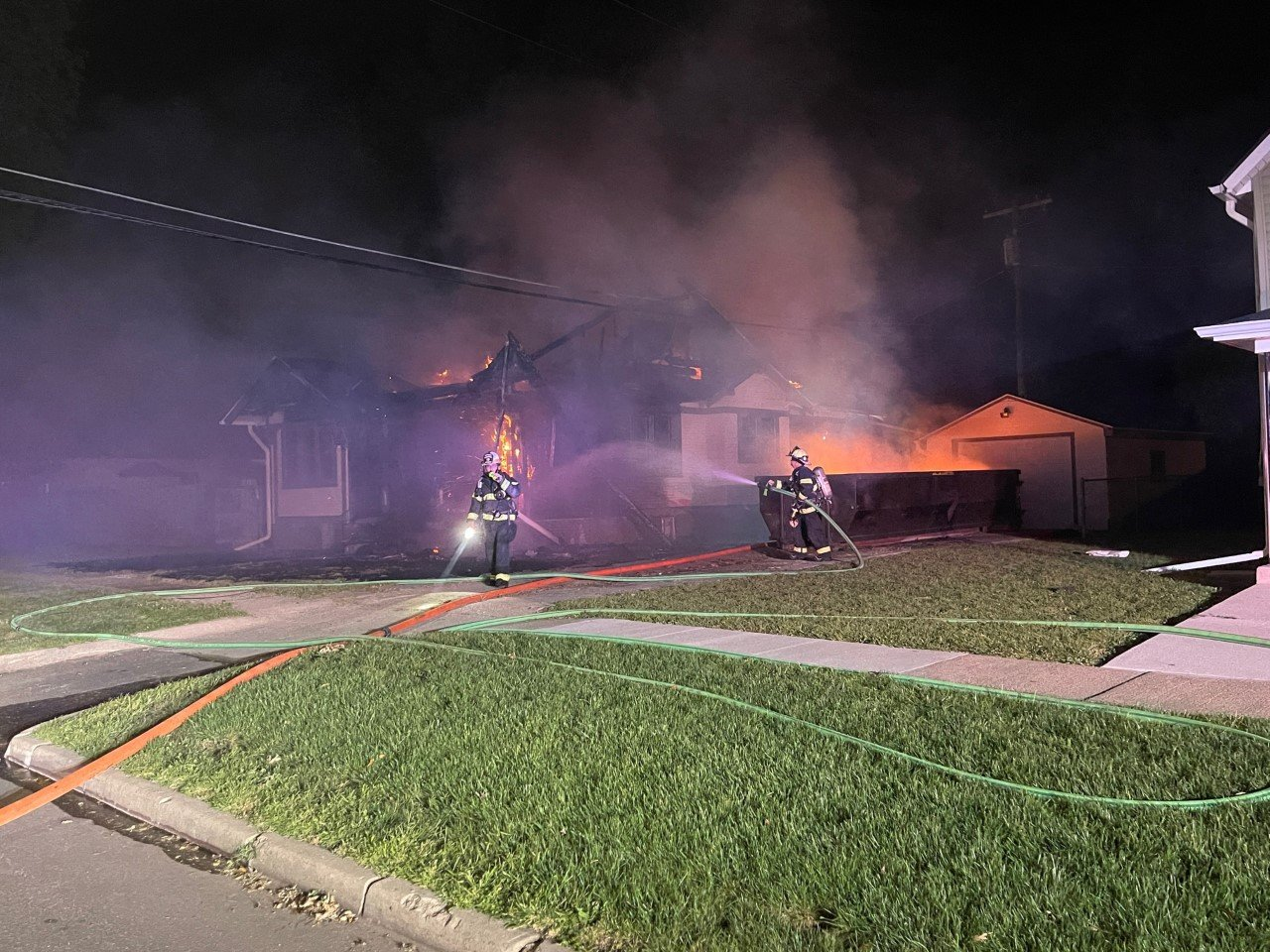 Firefighters fighting a structures fire with visible damage to the structure.